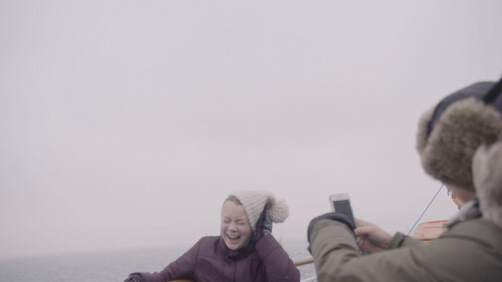 """Greta Thunberg auf einem Boot bei stürmischer See, hält lachend ihre Mütze fest, ein Begleiter filmt sie mit dem Handy, Filmszene aus """"I am Greta"""""""