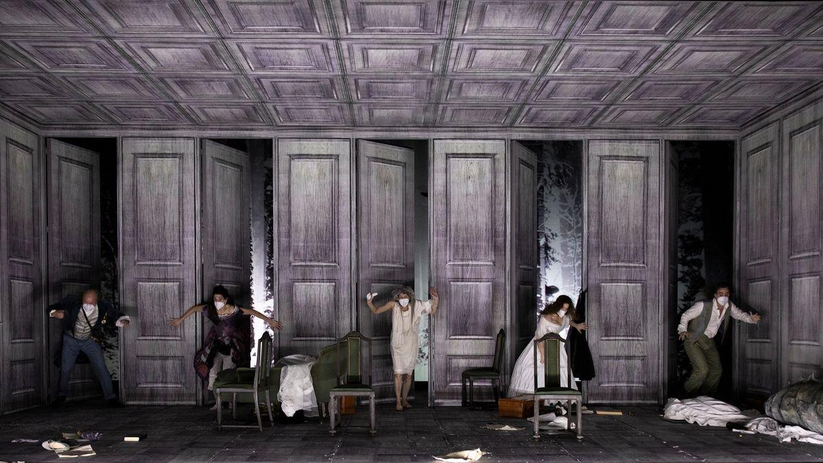 """5 kostümierte, maskierte Menschen kommen aus 5 nebeneinanderliegenden Türen: Szene aus """"Isola"""" am Staatstheater Nürnberg"""