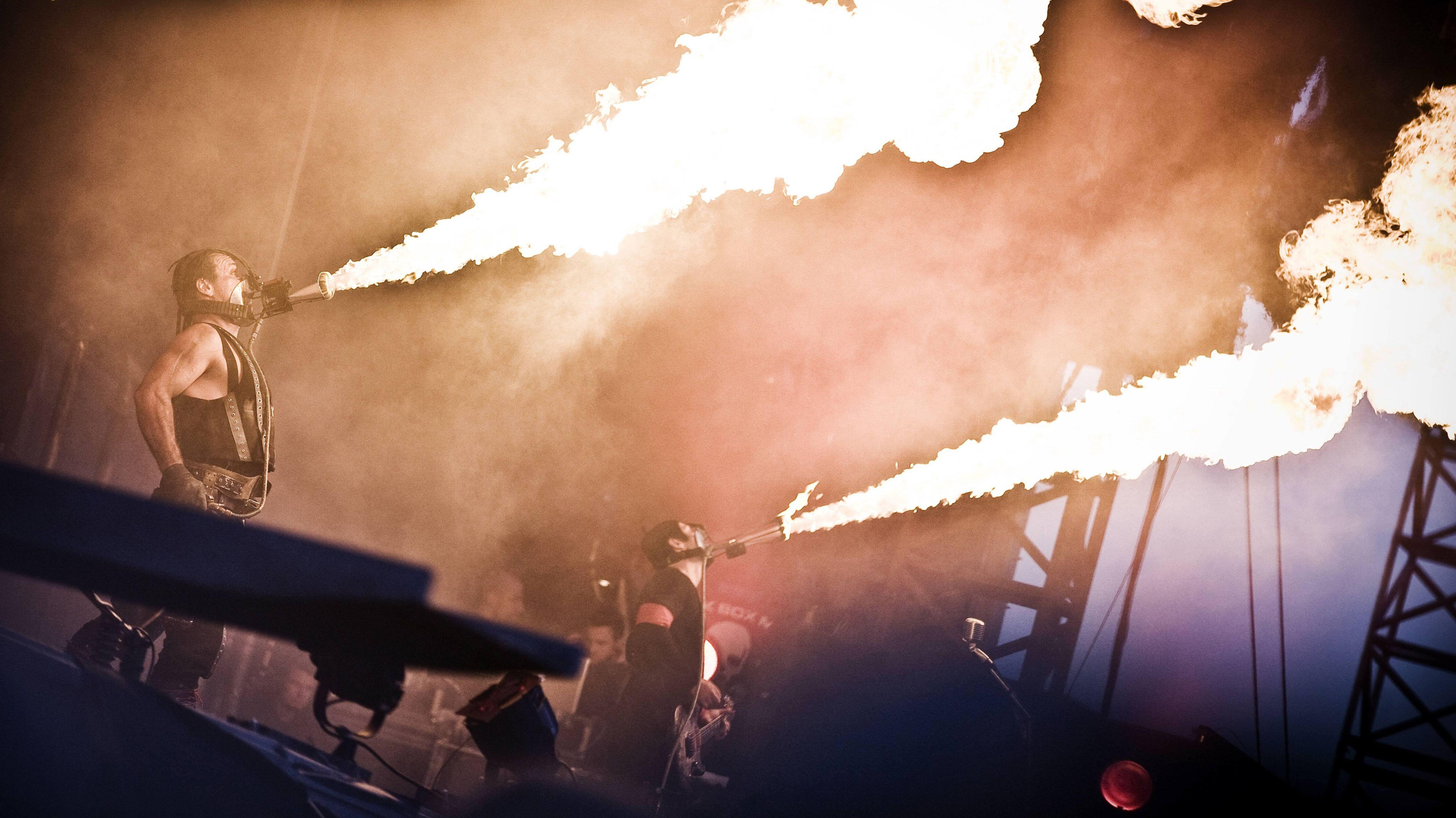 Rammstein-Bandmitglieder sprühen Flammen von der Bühne.