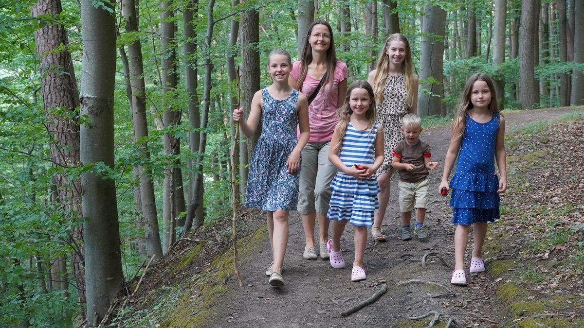 Familie Wege wandert auf dem Schlangenweg. Der Trampelpfad schlängelt sich am bewaldeten Hang entlang.