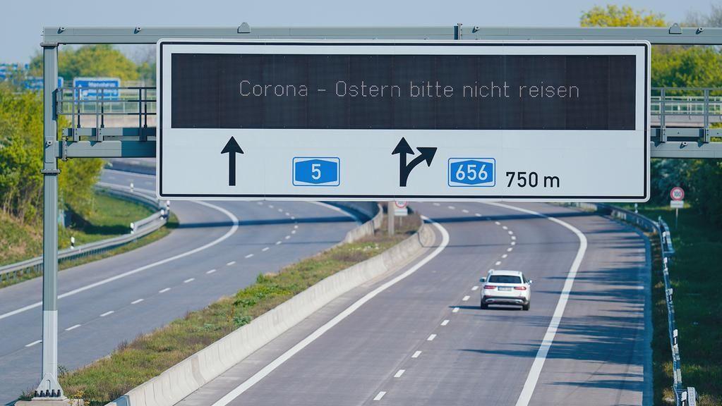 Anzeigetafel mit der Aufschrift ·Corona - Ostern bitte nicht reisen·