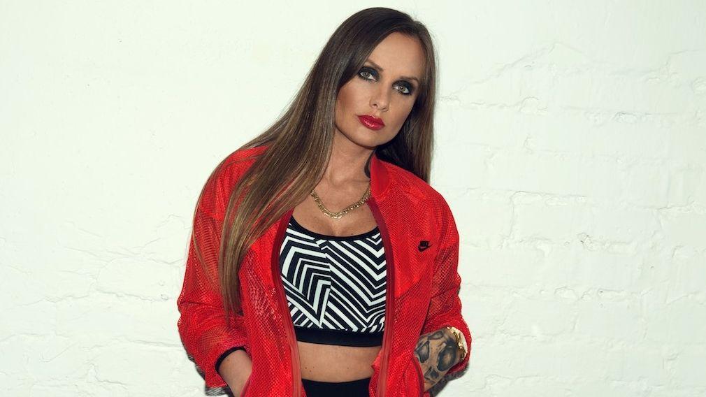 Rapperin Schwesta Ewa steht in einer roten Bomberjacke vor einer Wand und schaut herausfordernd in die Kamera.
