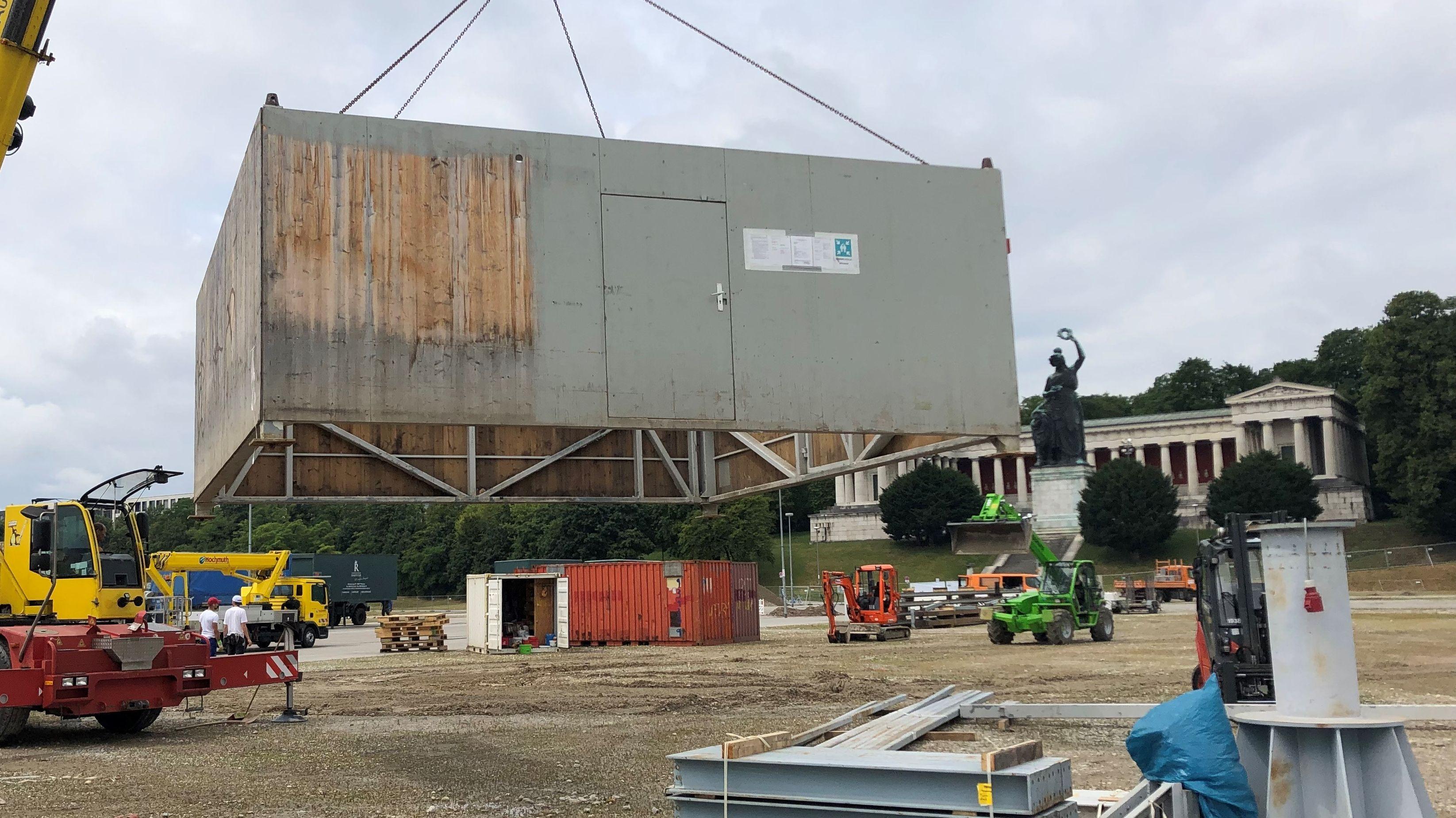 Vor der Bavaria hebt ein Kran gerade die ersten Container auf die Theresienwiese.