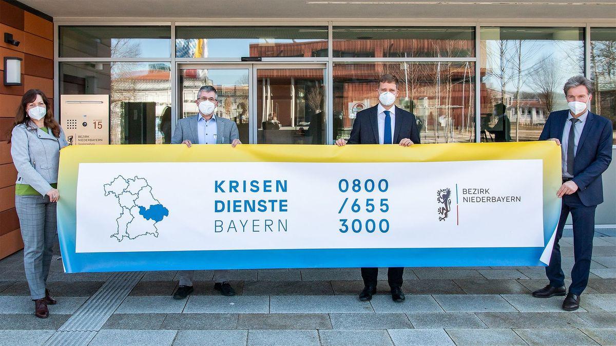 Claudia Holzner, Psychiatriekoordinatorin, Stefan Eichmüller, Olaf Heinrich, Thomas Pfeffer mit einem Plakat des Krisendienstes