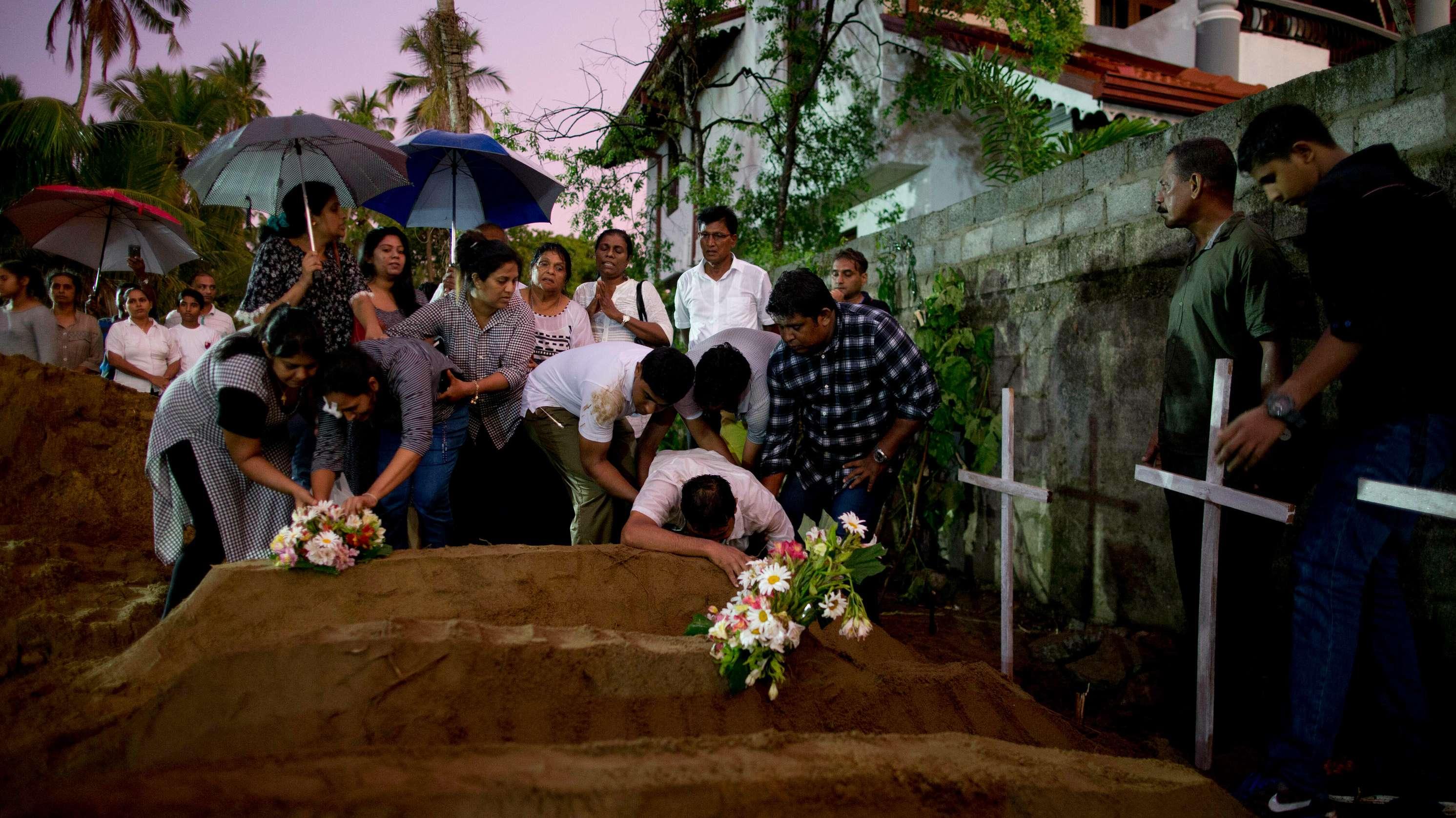 Verwandte platzieren Blumen nach der Beerdigung von drei Opfern derselben Familie, die bei der Bombenexplosion am Ostersonntag in der St.-Sebastians-Kirche in Negombo starben.