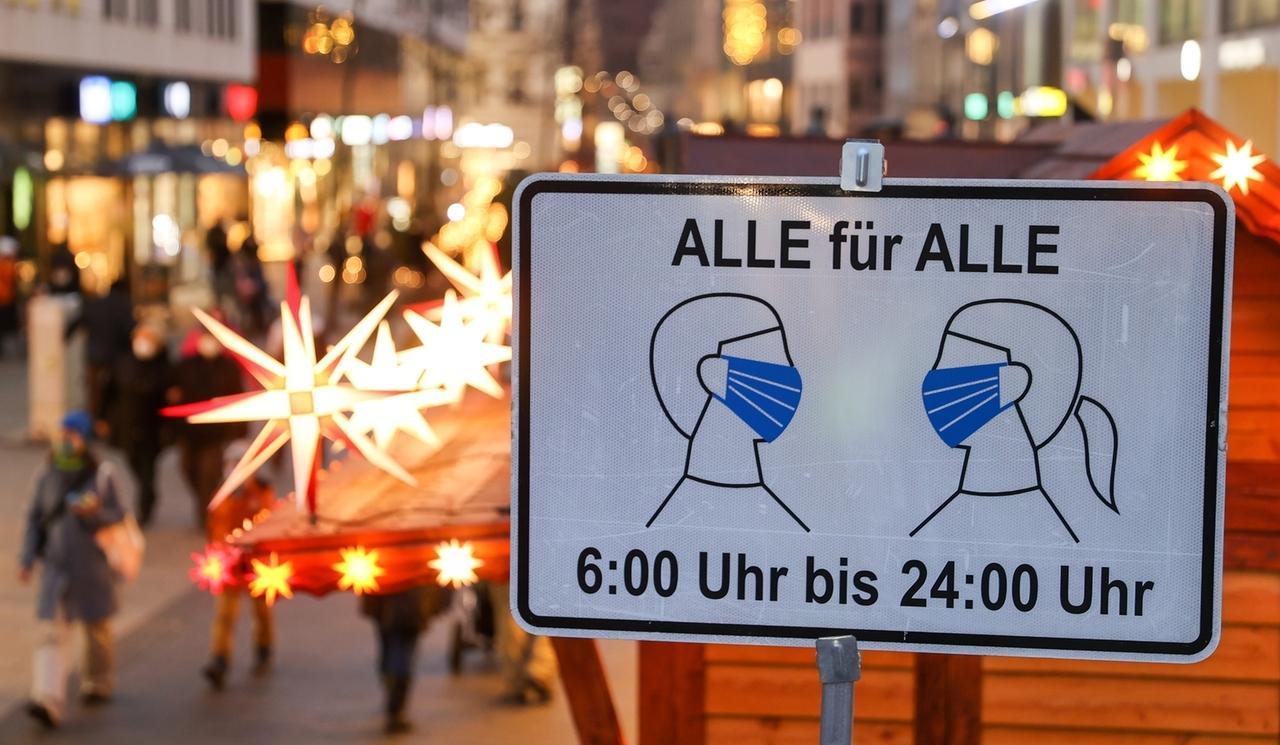"""Schild mit derAufschrift """"Alle für Alle - 6:00 bis 24:00 Uhr"""", das auf die Maskenpflicht hinweist, vor Fußgängerzone mit Weihnachts-Deko"""