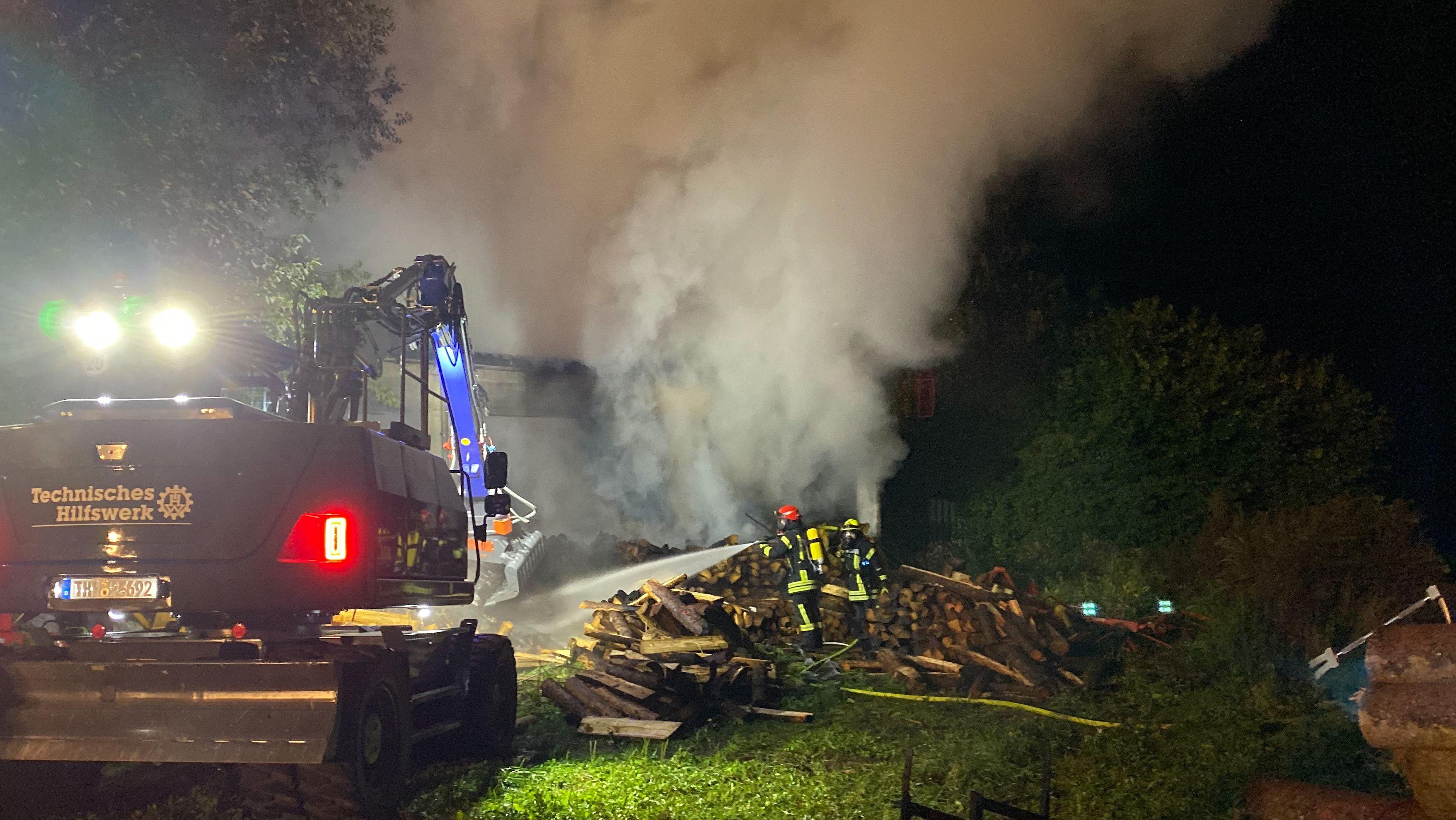 Ein Bagger des THW und Einsatzkräfte der Feuerwehr beim Löschen eines Brandes in Gessertshausen