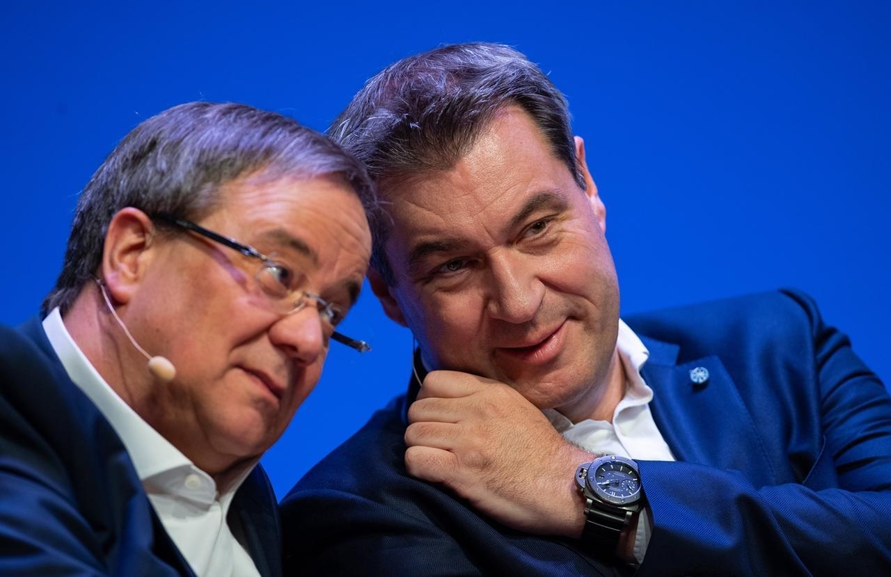 Nordrhein-Westfalen, Münster: Armin Laschet (CDU, l), Ministerpräsident des Landes Nordrhein-Westfalen, und Markus Söder (CSU), Ministerpräsident des Landes Bayern, sitzen beim offiziellen Start der Unions-Parteien zum Europawahlkampf auf der Bühne. (zu dpa «Söder gratuliert Laschet launig zum 60.: Feiern - «aber mit Abstand»») Foto: Guido Kirchner/dpa +++ dpa-Bildfunk +++