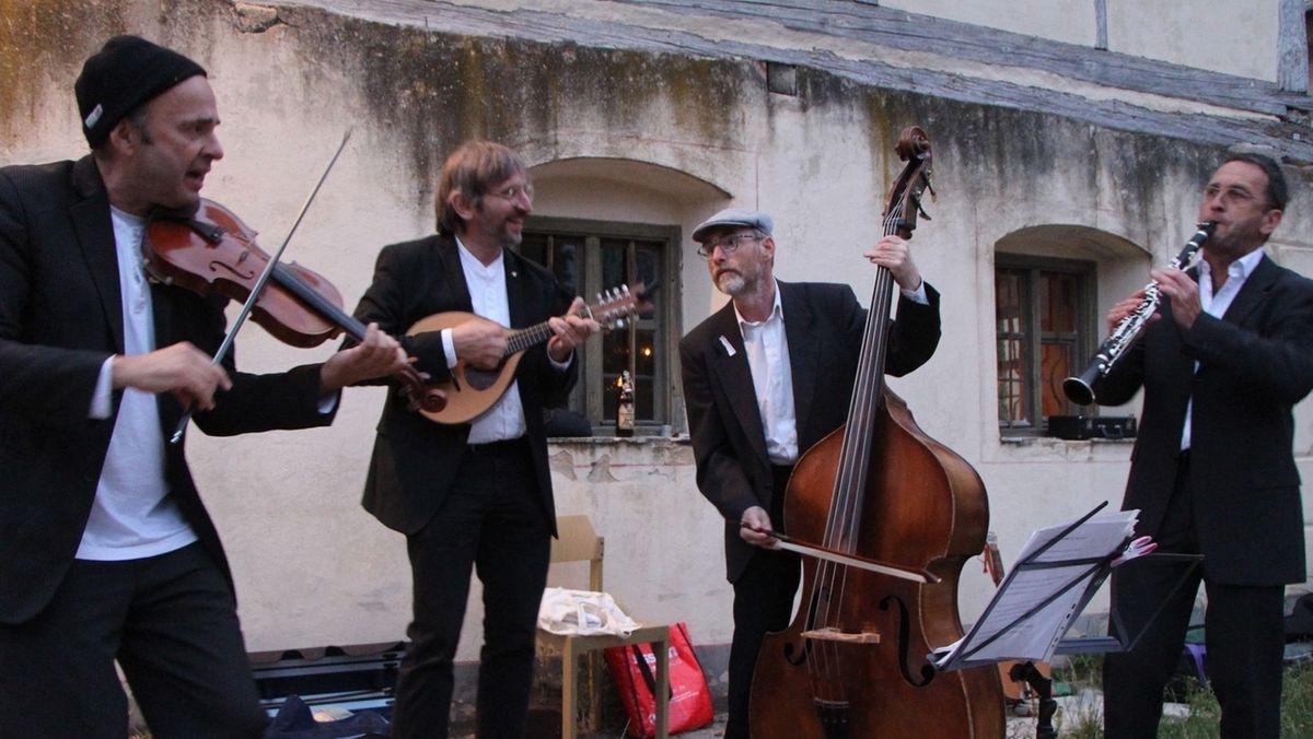 Vier Musiker mit Streich-, Zupf- und Blasinstrumenten.