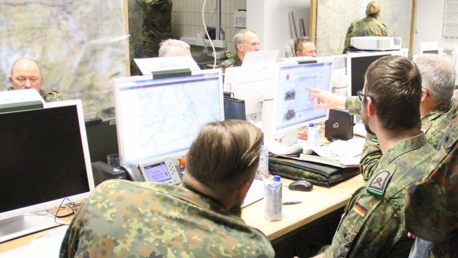 Bundeswehrsoldaten sitzen in einem Container vor Bildschirmen.