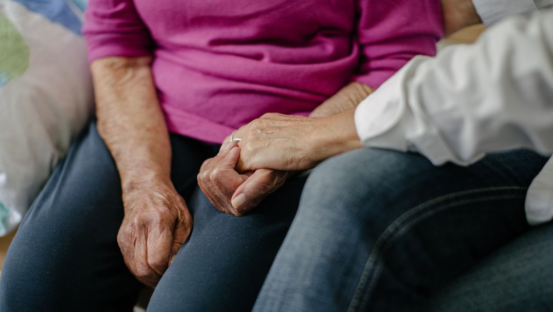 Eine Pflegerin hält die Hände einer Seniorin.