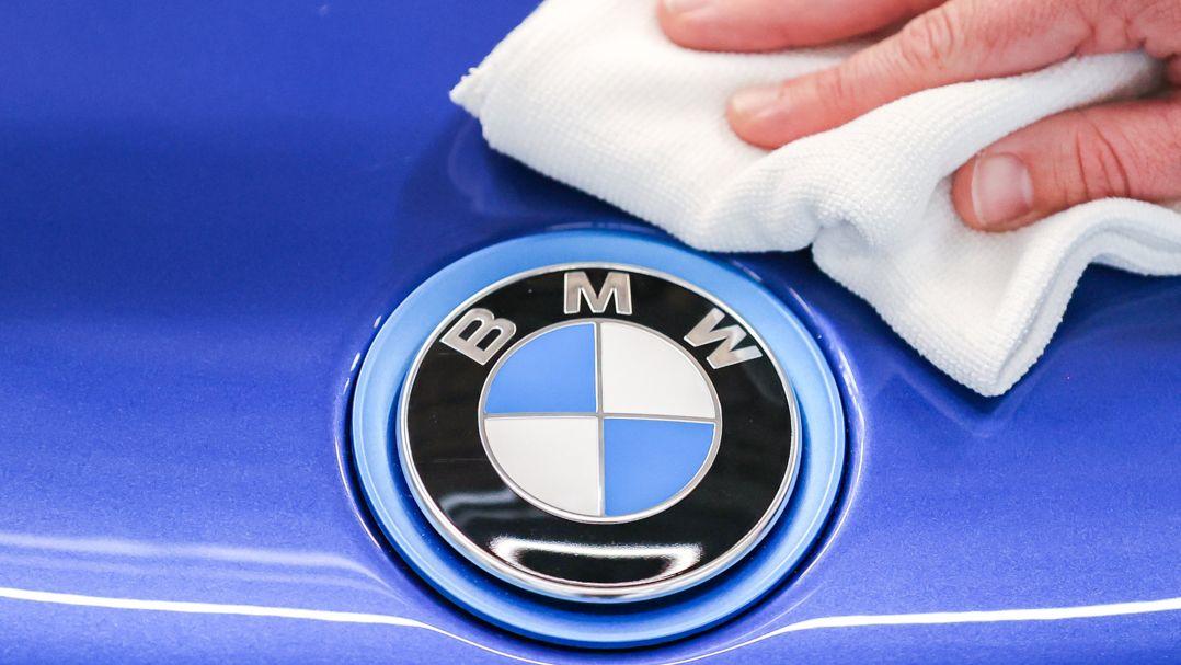 Ein Mitarbeiter von BMW poliert mit einem Tuch das Logo von einem BMW i8.