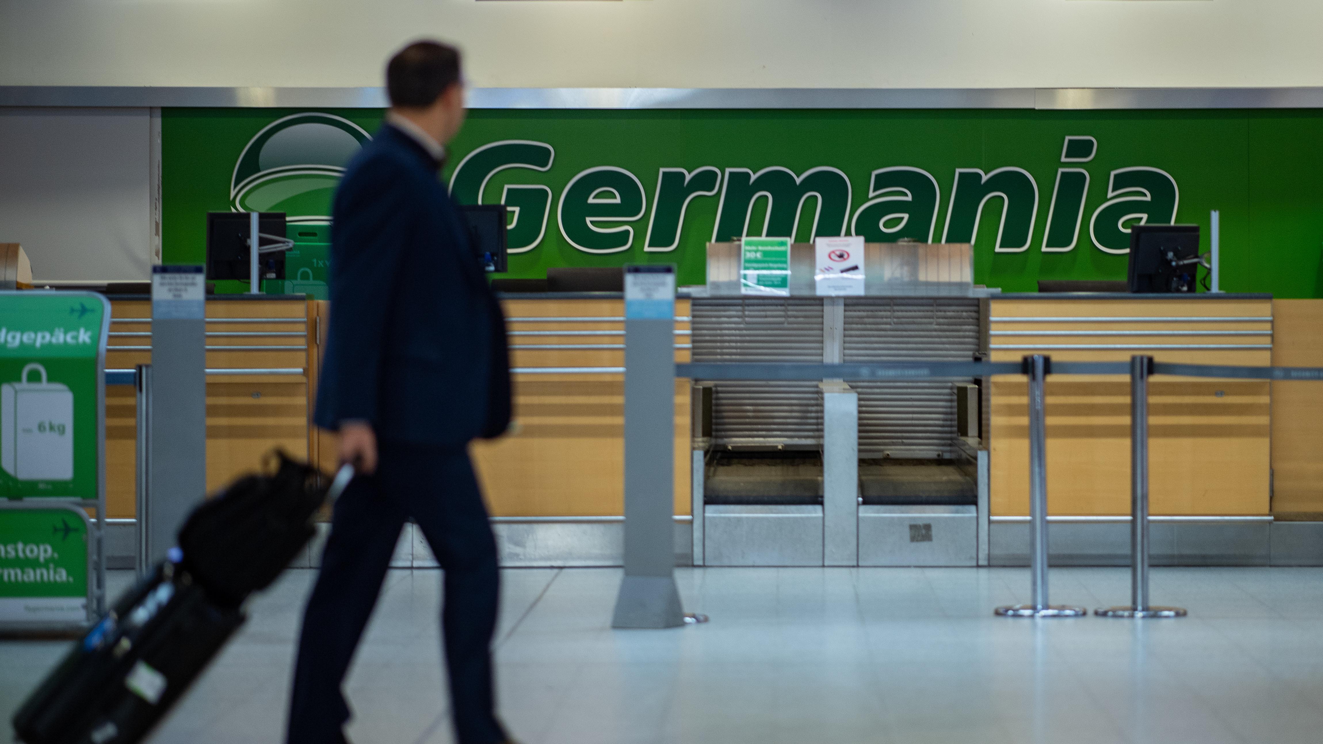 Fluggast geht an einem geschlossenen Germania-Schalter vorbei.