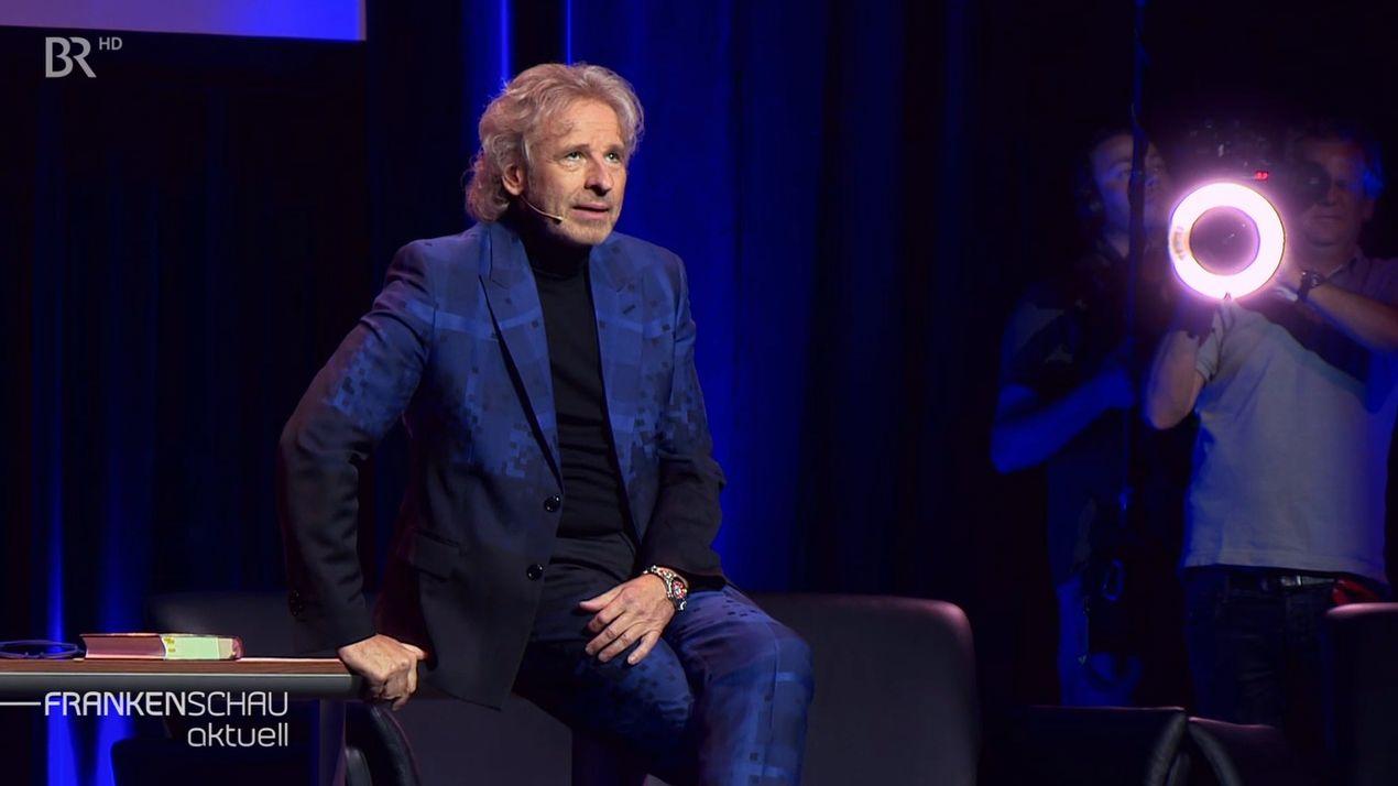 Thomas Gottschalk im dunkelblauen Anzug sitzt in einem Fernsehstudio, mit der Hand stützt er sich auf einem Tisch ab, auf dem ein Buch liegt.