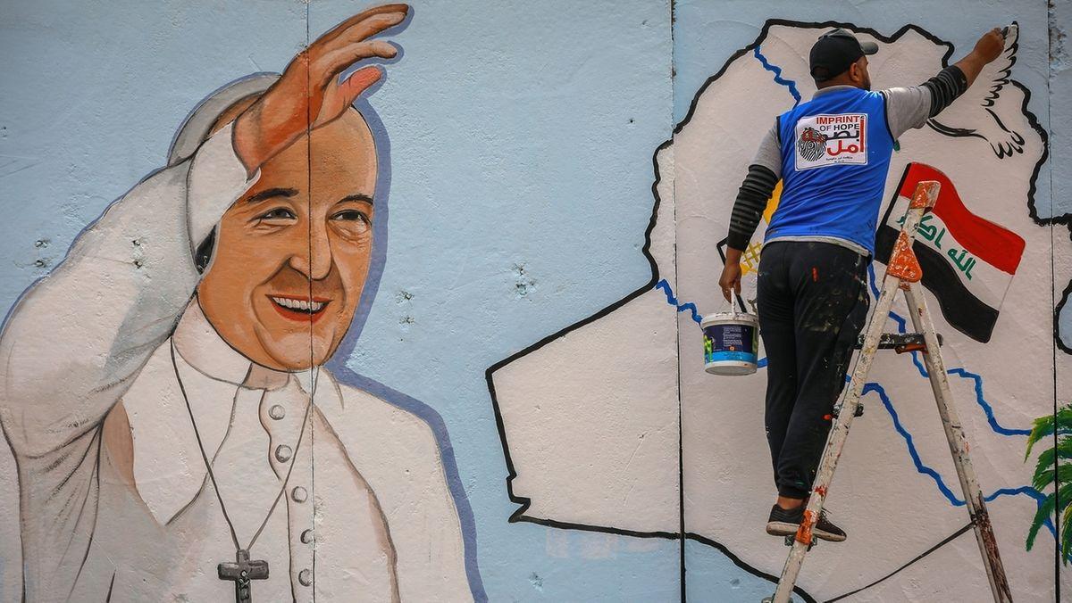 """Amjad, ein irakischer Künstler der NGO """"Imprint of Hope"""", malt ein Wandbild von Papst Franziskus an eine Wand vor der """"Sayidat-al-Nejat Kathedrale"""" (Kathedrale Unserer Lieben Frau der Erlösung) in Bagdad."""