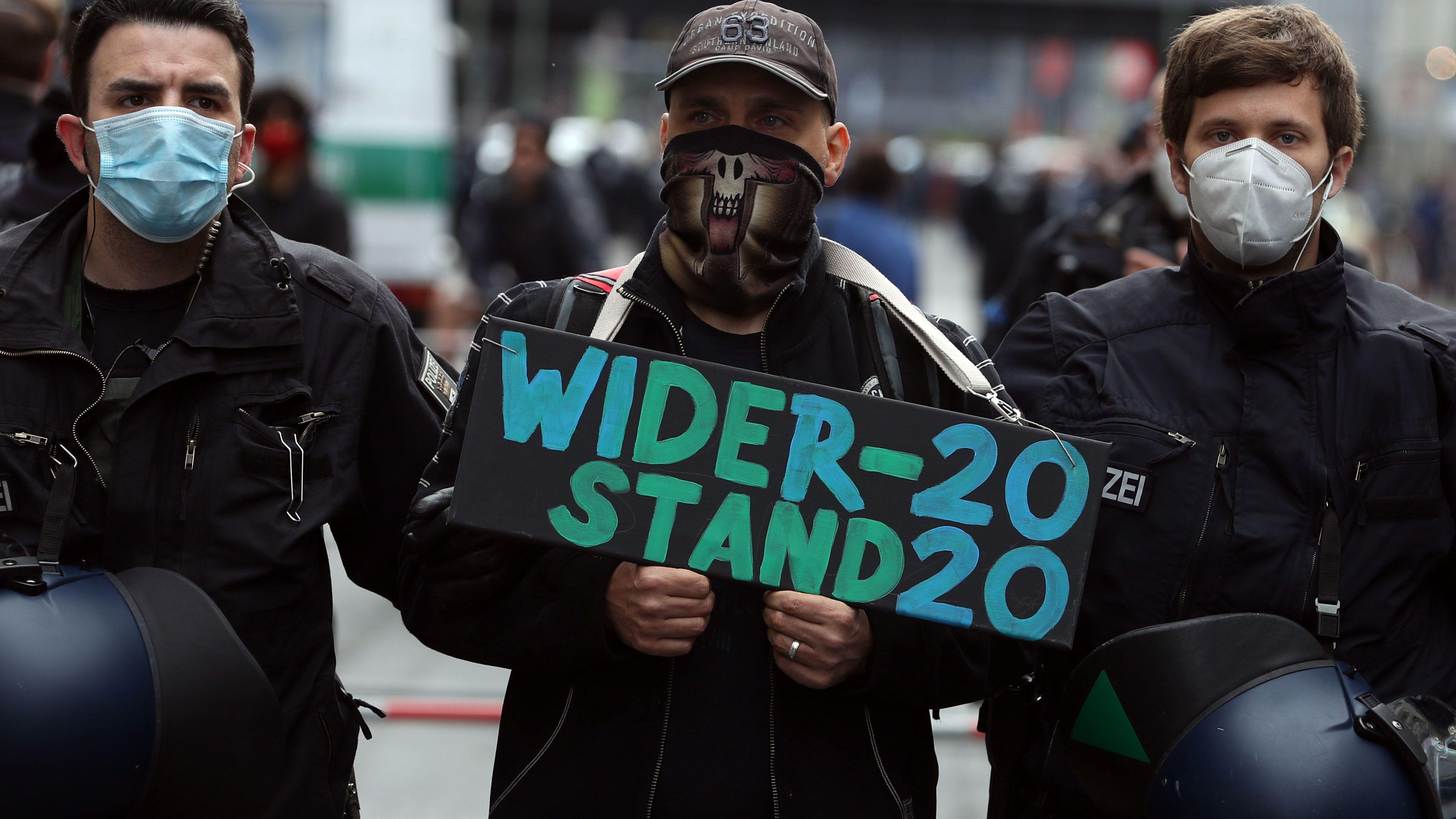 """Ein Demonstrant wird in Berlin abgeführt, während er ein Schild hält mit der Aufschrift """"Widerstand - 2020""""  hochhält."""