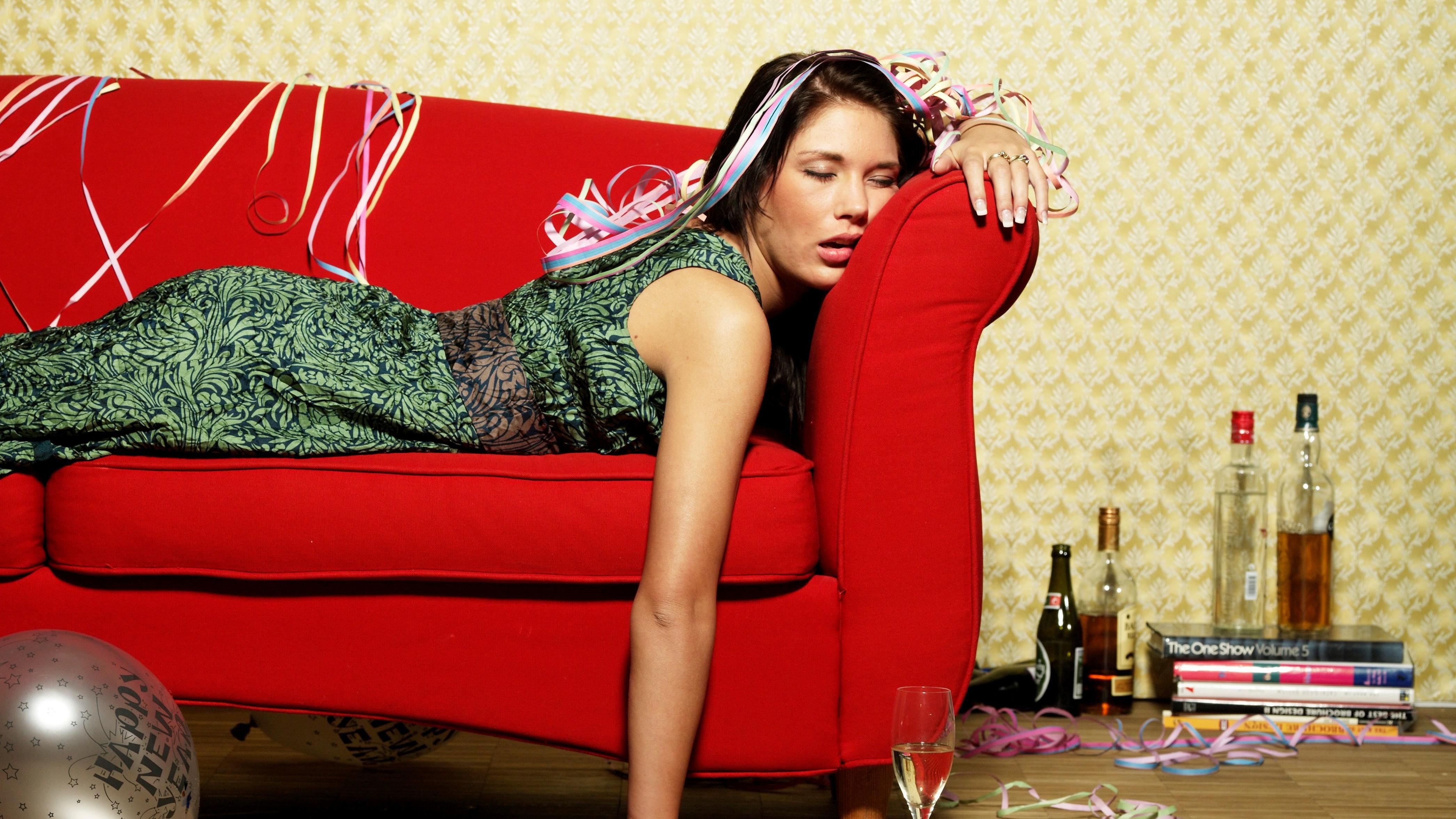Frau liegt schlafend auf einem Sofa. Alkoholflaschen stehen daneben.