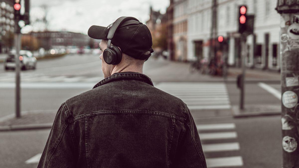Ein junger Mann hört mit Kopfhörern Musik von seinem Smartphone.