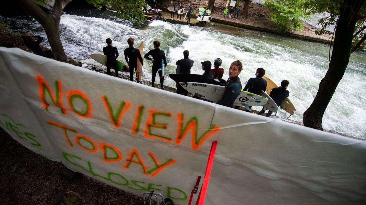 Surfer demonstrieren an Münchner Eisbachwelle