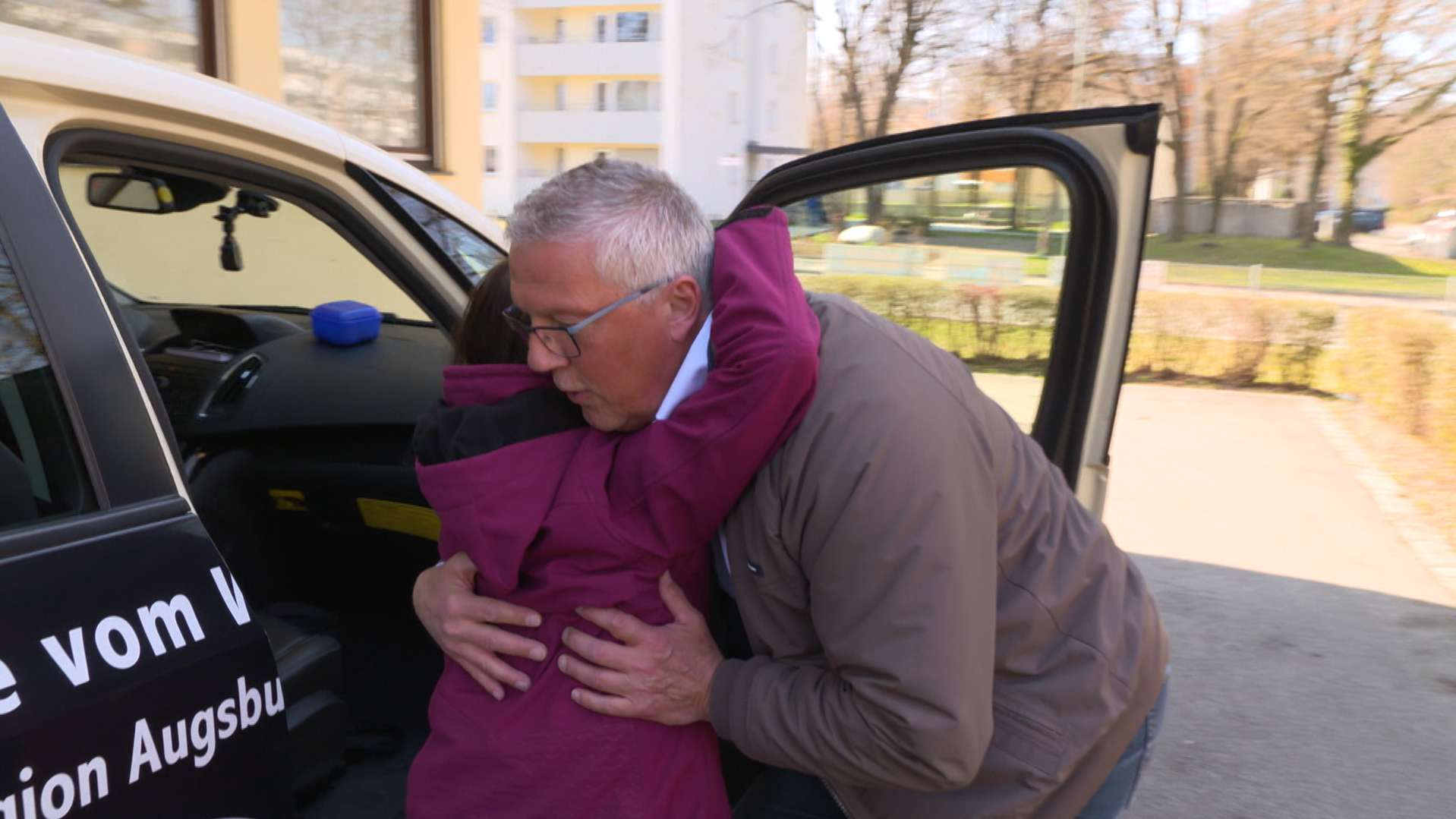 Taxifahrer hilft Patientin ins Taxi