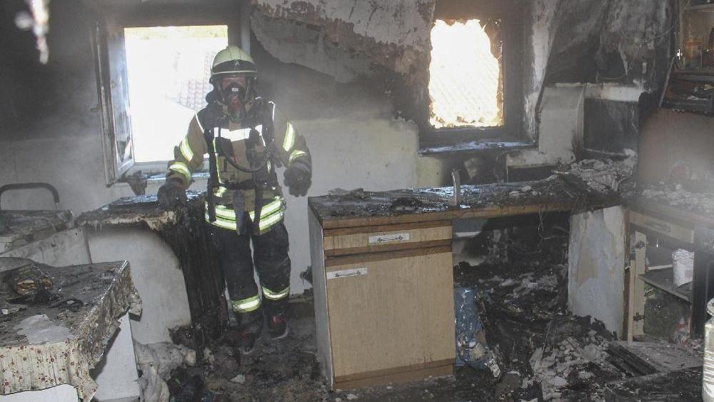 Ein Feuerwehrmann steht in der total ausgebrannten Wohnung