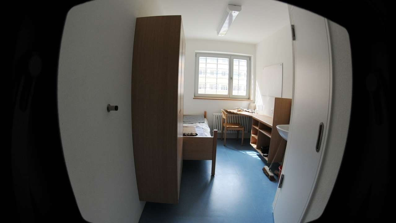 Blick durch eine Öffnung in der Tür in eine Gefängniszelle in der Justizvollzugsanstalt Landshut