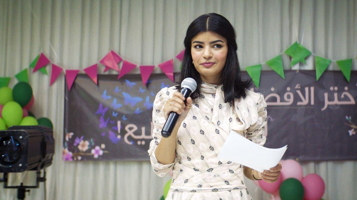 In einem schicken weißen Kleid steht die junge Ärztin Maryam mit Mikrofon auf einer Bühne und macht Wahlkampf