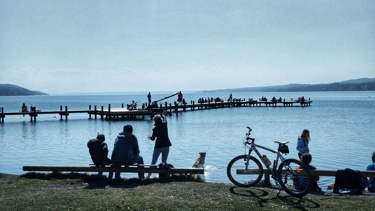 Menschen sitzen am Ufer des Starnberger Sees. (Archivbild)