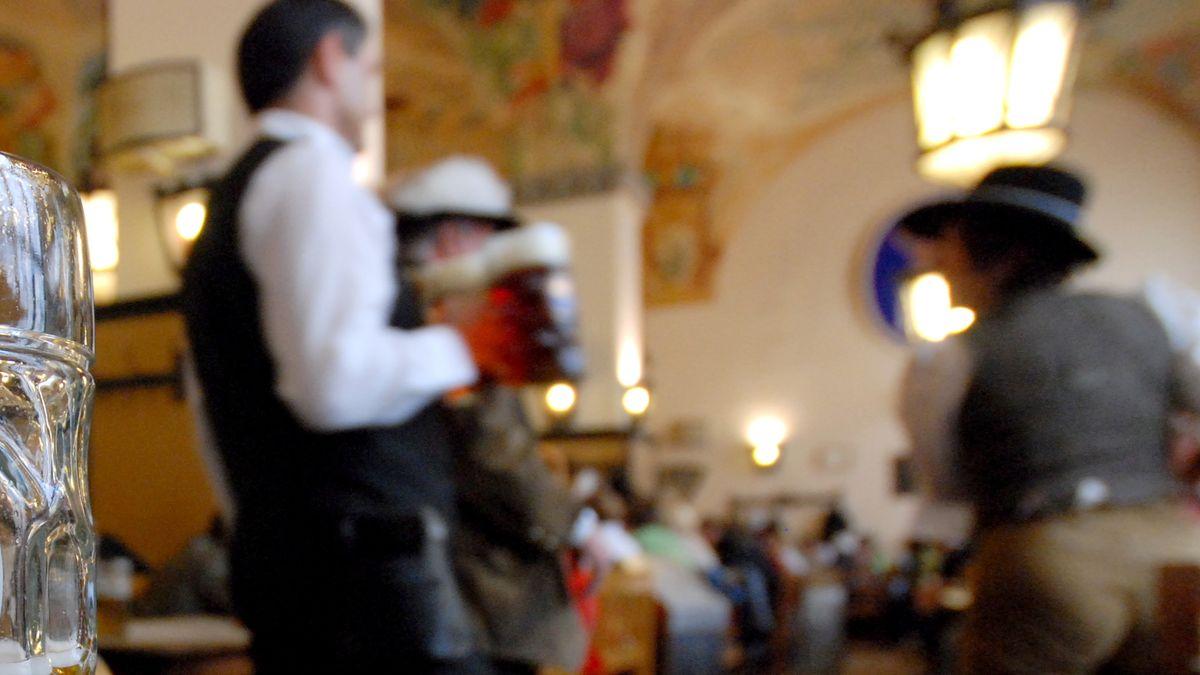 Ein Kellner trägt Bierkrüge durch einen Wirtsraum.