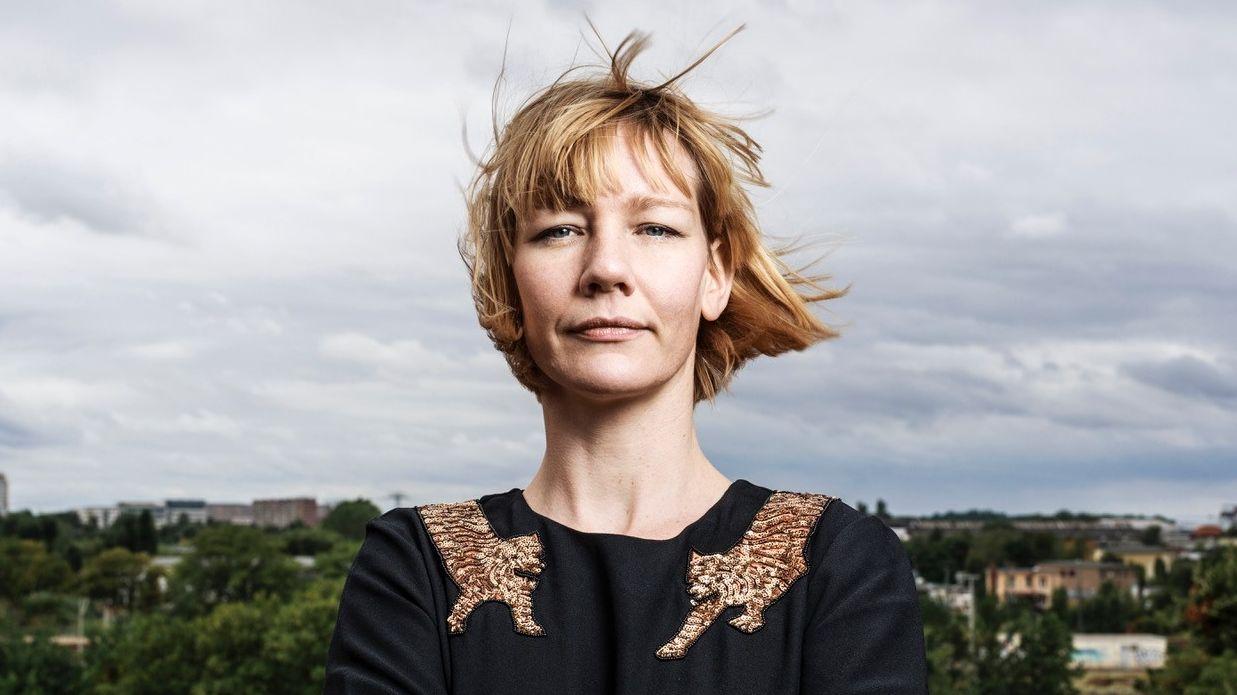 Die Schauspielerin Sandra Hüller im Tiger-Sweatshirt mit wehenden Haaren auf einem Hügel von Rom