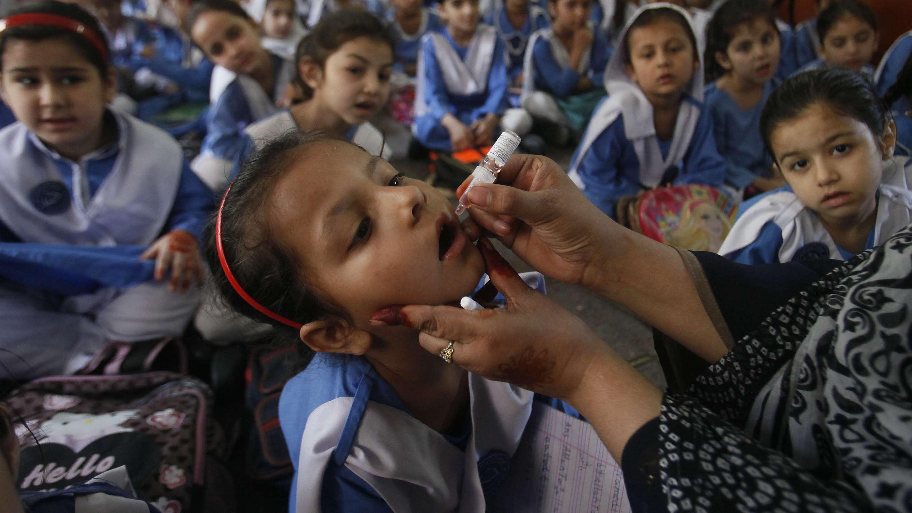 Pakistan: Eine medizinische Mitarbeiterin impft eine Schülerin gegen Polio. Eine Helferin wurde nun in Pakistan erschossen. (Symbolbild)