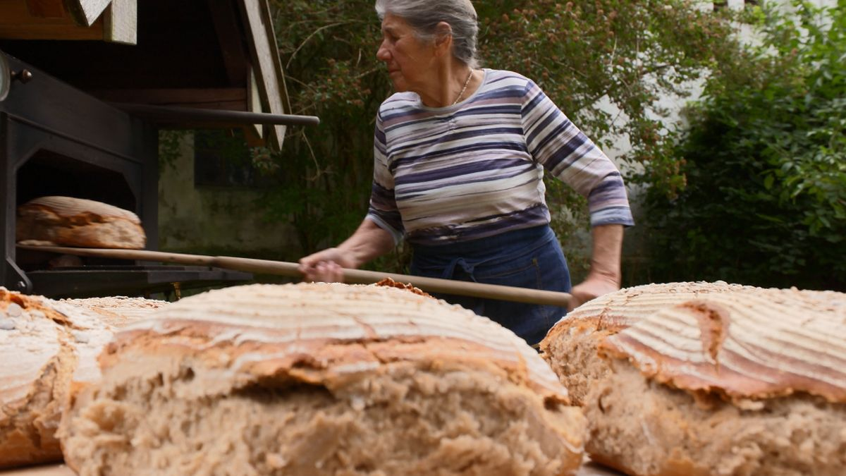 Bäuerin Resi Reichl holt ihr frischgebackenes Brot aus dem Ofen