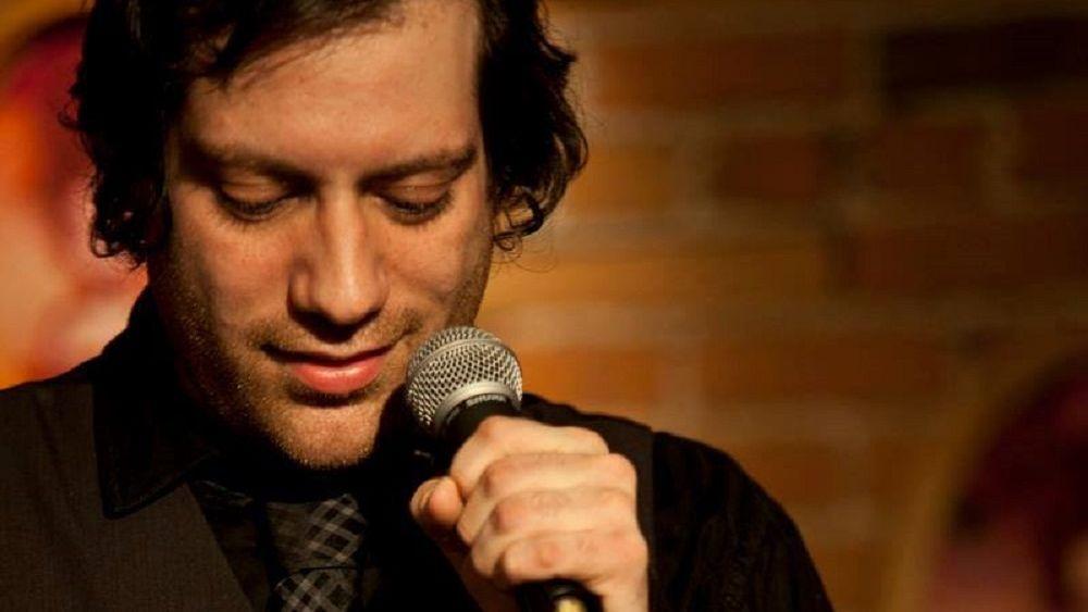 Ein Mann im dunklen Hemd, karierter Krawatte am Mikrofon.