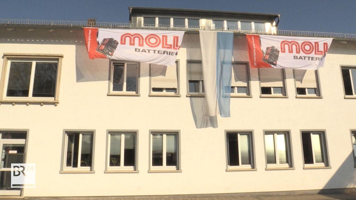 """Transparente mit der Aufschrift """"Moll Batterien"""" hängen an der Fassade eines Gebäudes."""