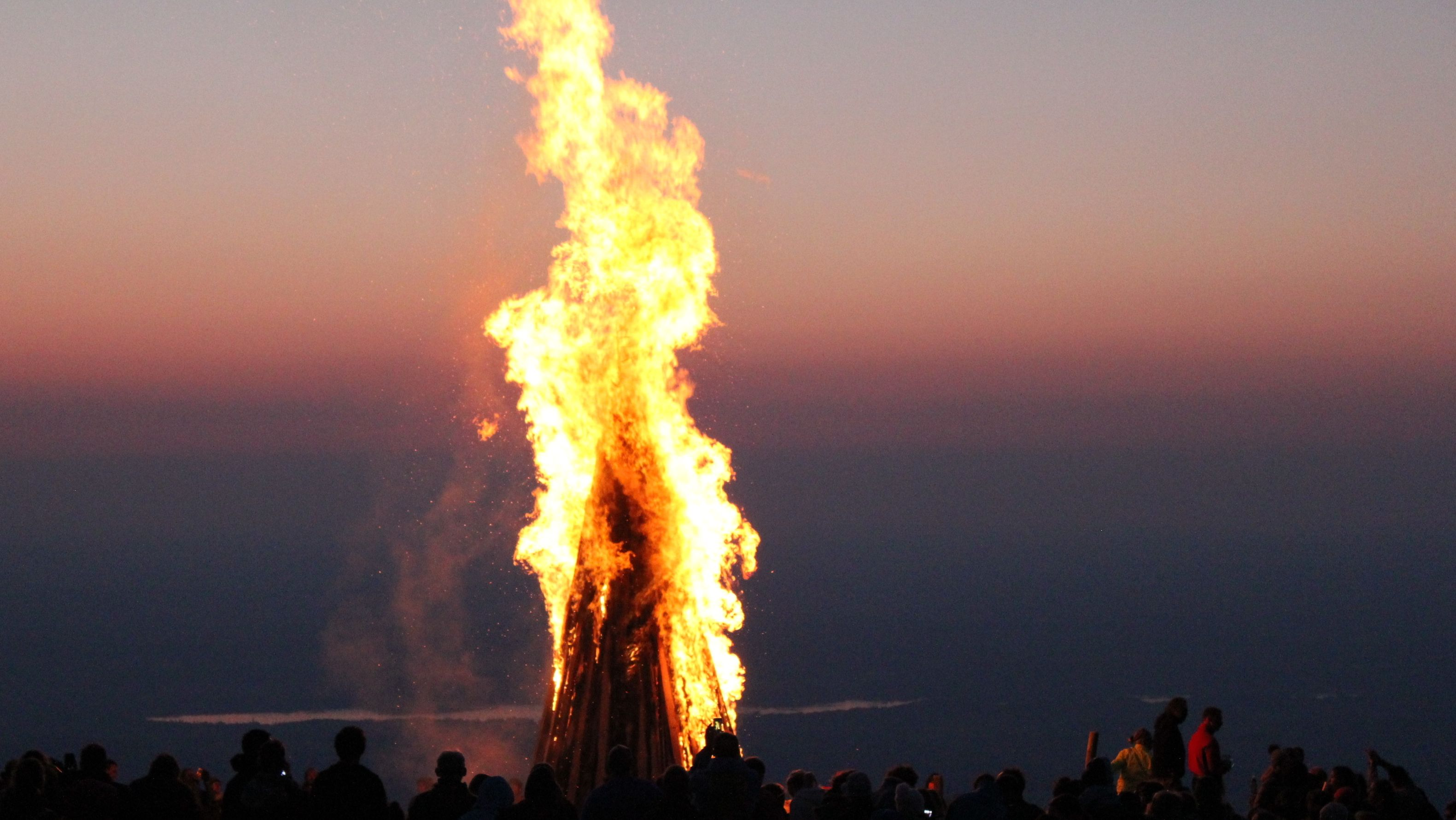 Menschen stehen um ein Sonnwendfeuer (Symbolbild).