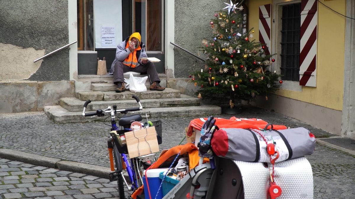 Mann sitzt auf Steinstufen vor Haus, davor bepacktes Fahrrad