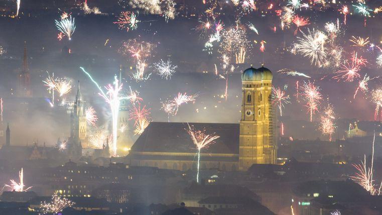 Feuerwerksraketen explodieren in einer Silvesternacht über der Innenstadt von München.