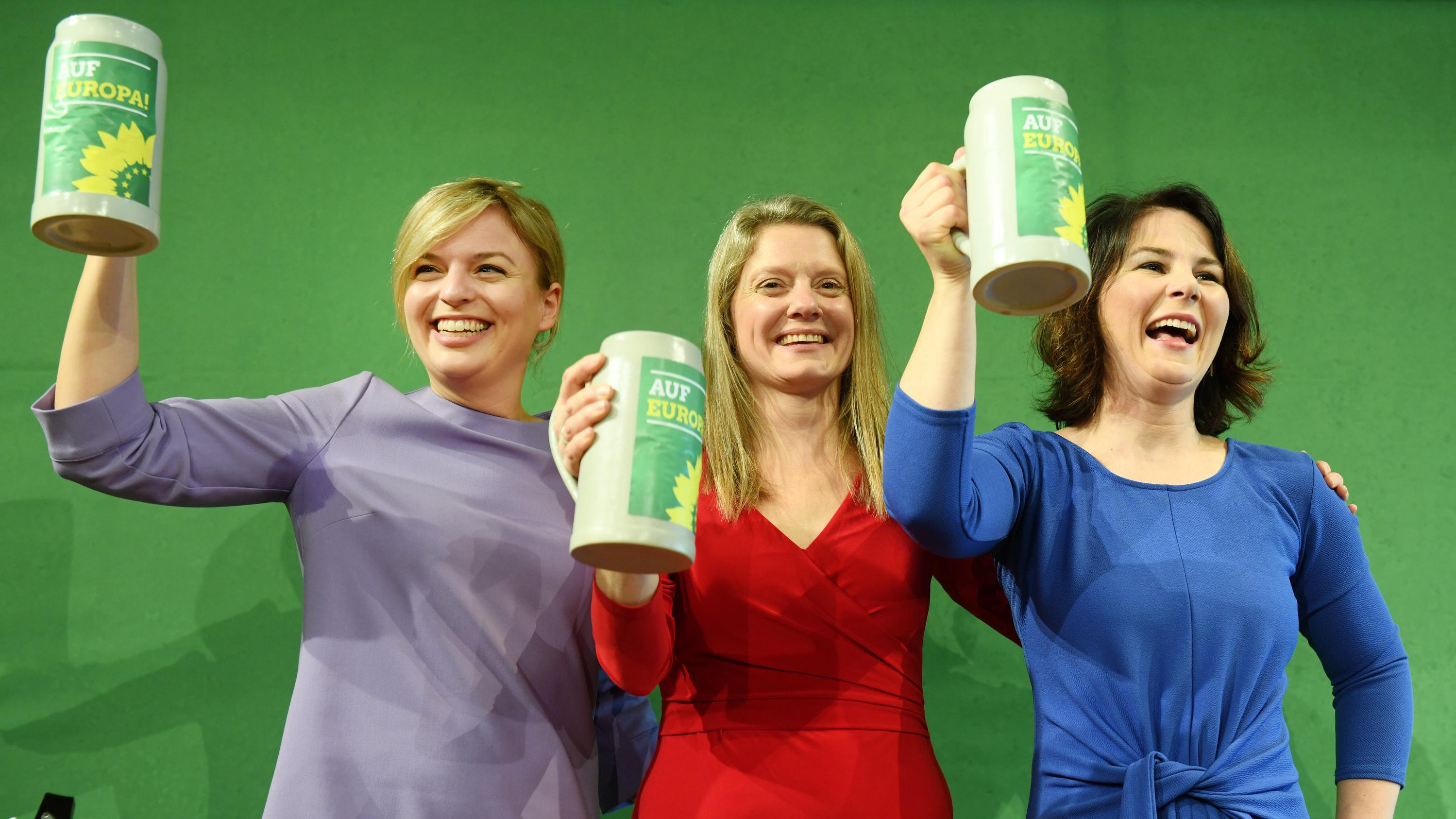 Grüne Politikerinnen halten Bierkrüge in den Händen