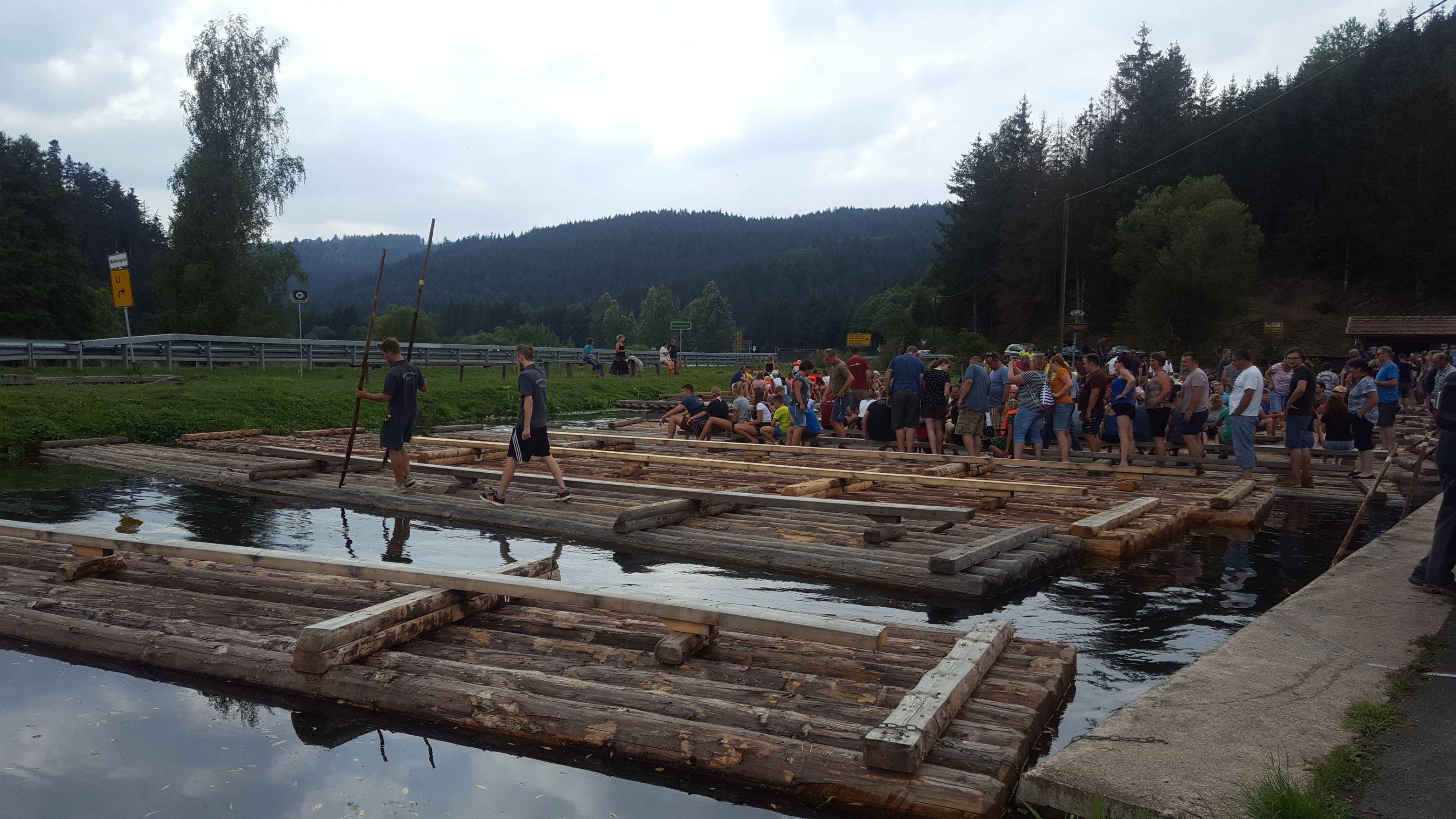 Menschen betreten Floße, die im Wasser liegen.