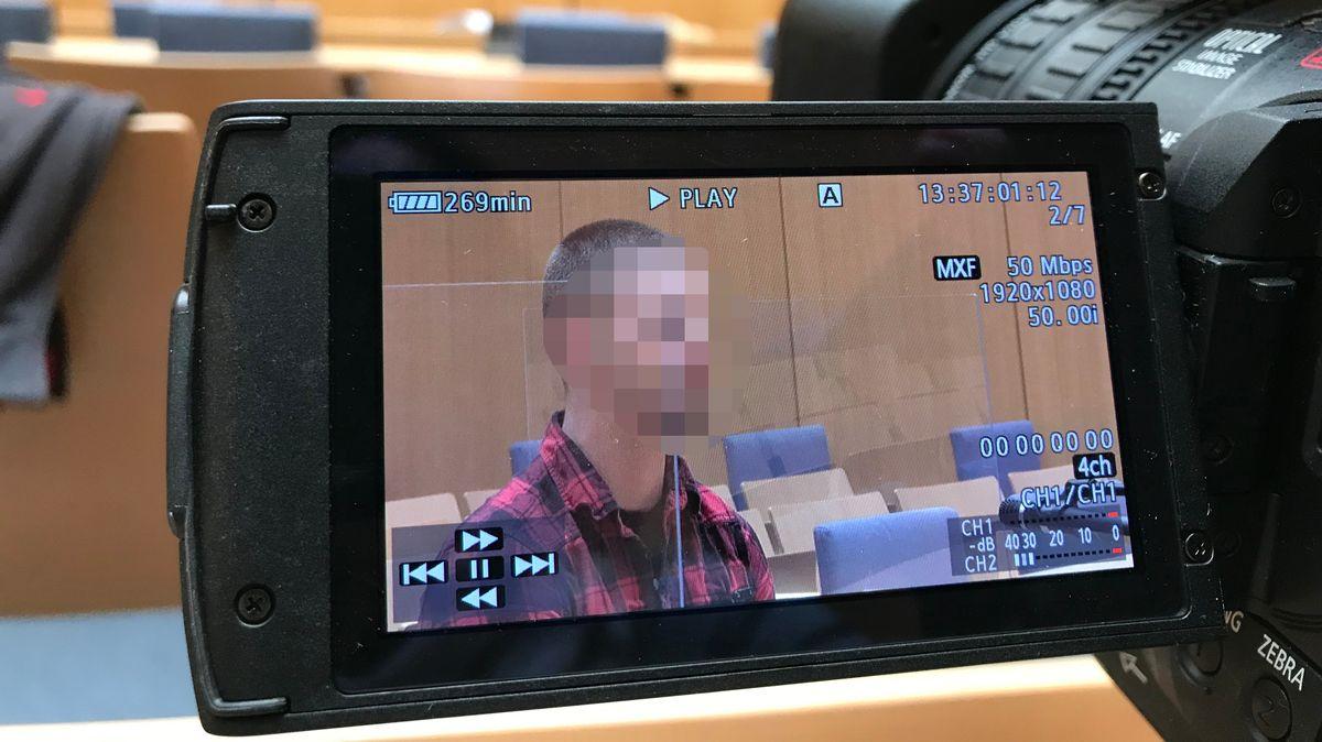 Der Monitor einer Kamera zeigt einen mit einem roten Karohemd gekleideten Mann, der in einem Gerichtssaal auf der Anklagebank sitzt.