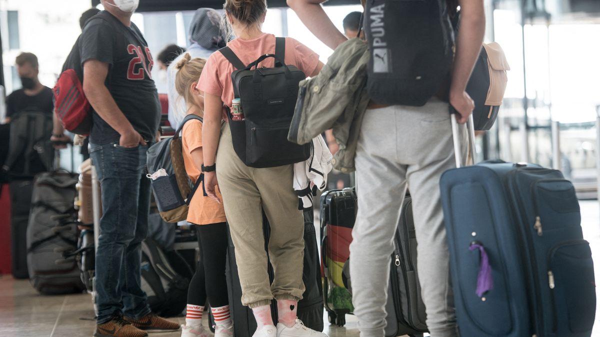 Urlauber stehen Schlange, um ihre Koffer an einem Check-in-Schalter des Willy-Brandt-Flughafen in Berlin aufzugeben.