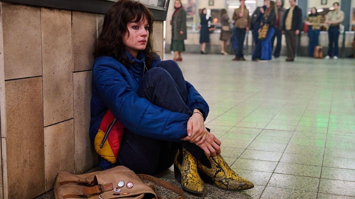 Eine junge Frau mit verheultem Gesicht und verlaufener Schminke sitzt in einem Bahnhofs-Untergeschoss