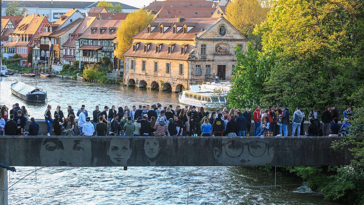 Zahlreiche junge Menschen stehen auf einer Brücke, im Hintergrund ein Ausflugsschiff.
