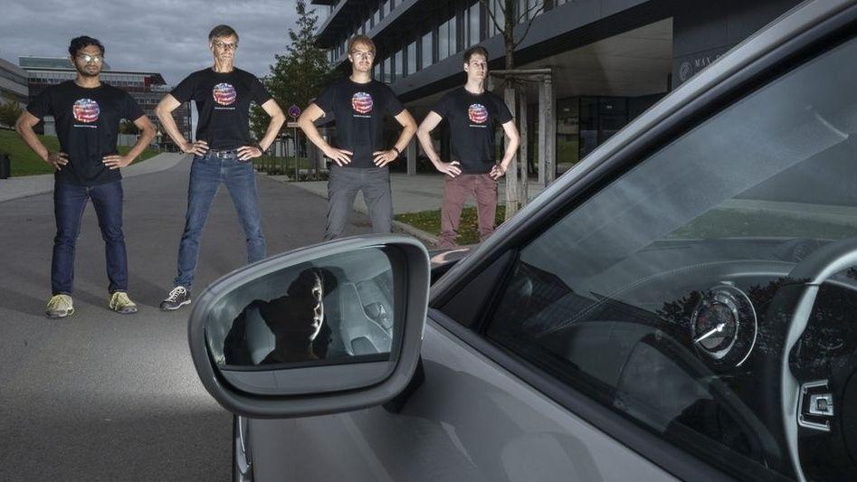 Die Wissenschaftler Anurag Ranjan (von links nach rechts), Michael J. Black, Andreas Geiger und Joel Janai stehen mit Farbflecken bedruckten T-Shirts vor einem Auto.