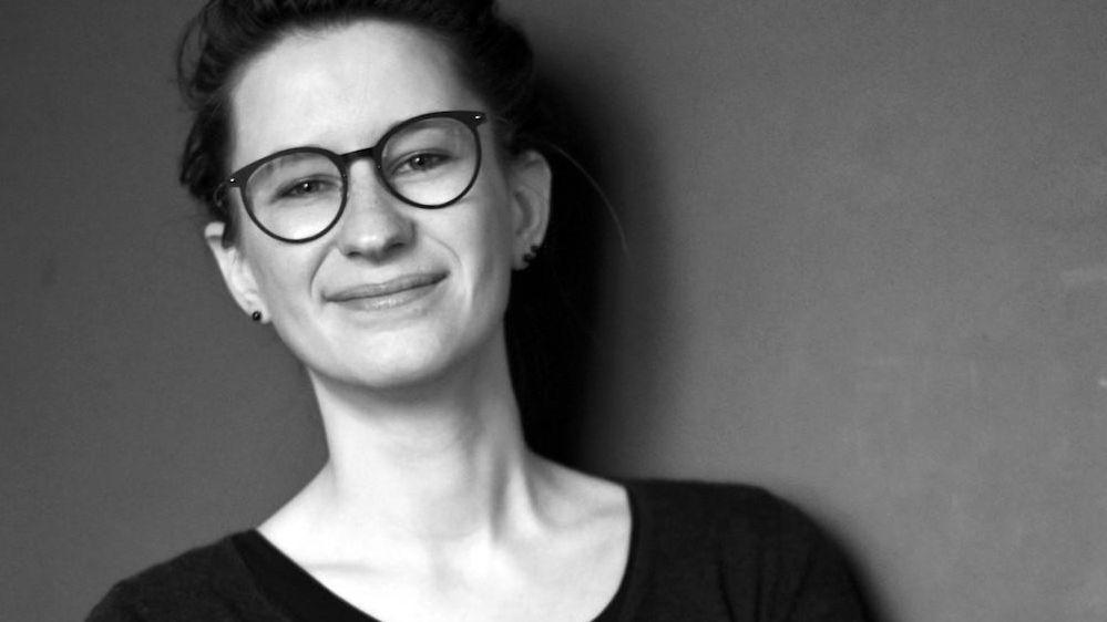 Schwarz-weiß-Foto von Lisa Frühbeis, junge, schlanke Frau mit Kurzhaarschnitt und Brille, lächelt.