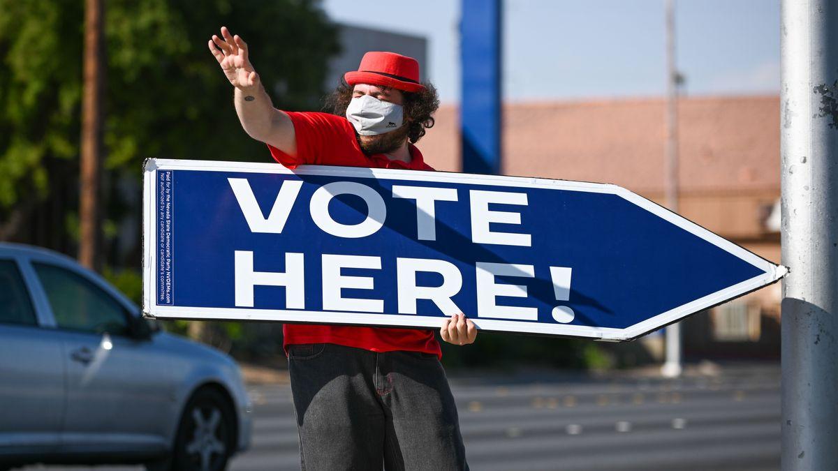 """Ein Mann animiert mit einem Schild """"Vote Here"""" zur Stimmabgabe für die US-Präsidentschaftswahl in Las Vegas, Nevada."""