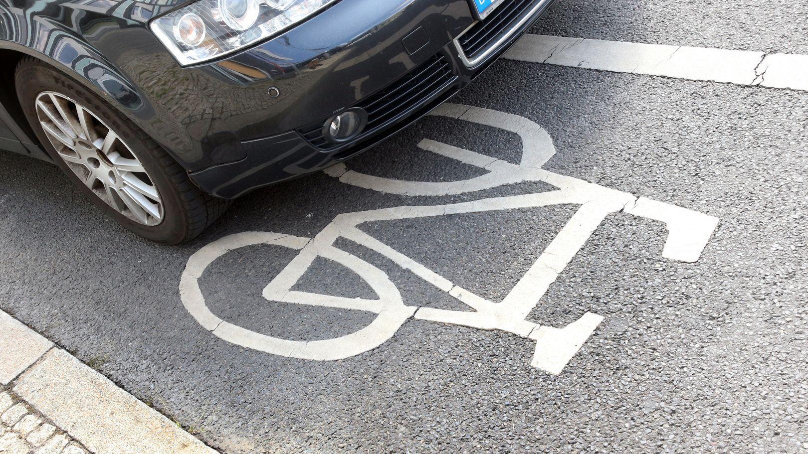 Ein Auto steht auf einer Fahrradspur.