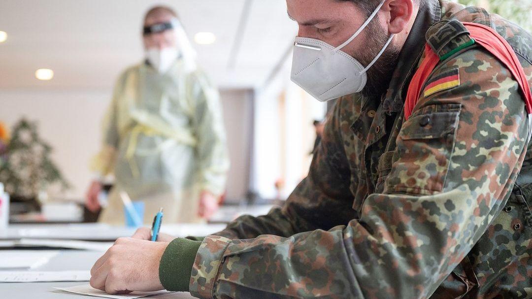 Ein Soldat füllt in einem Pflege- und Altenheim einen Zettel aus