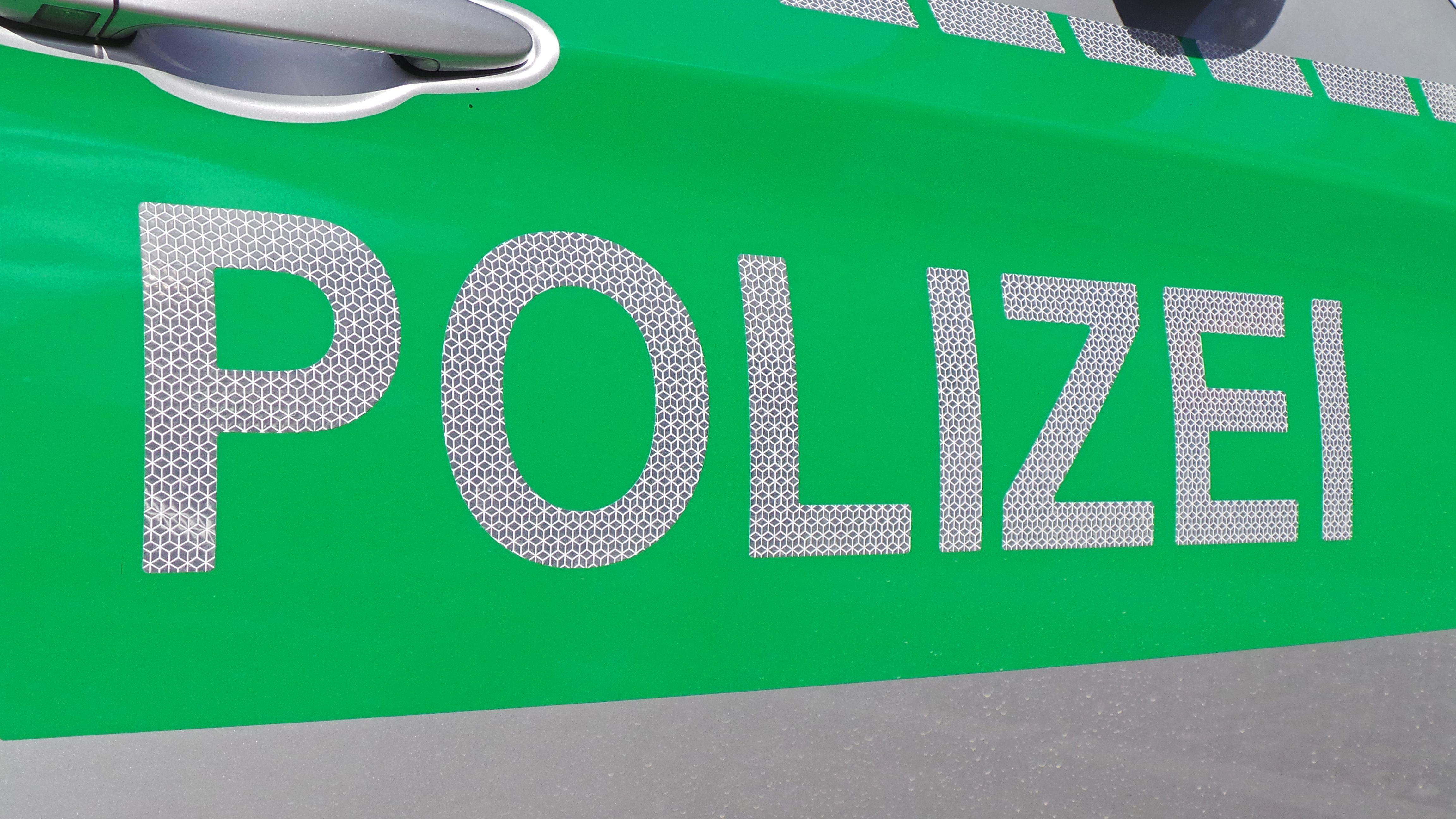 Schriftzug Polizei auf der Seite eines Polizeiautos