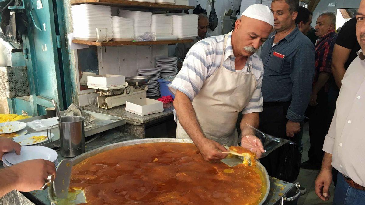 Eine große Portion Knafeh wird an einem Straßenverkauf in kleine Portionen geteilt und verkauft.